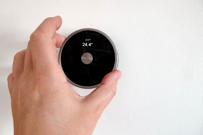 DIY Nest Thermostat with hand adjusting target temperature showing scale of circular housing