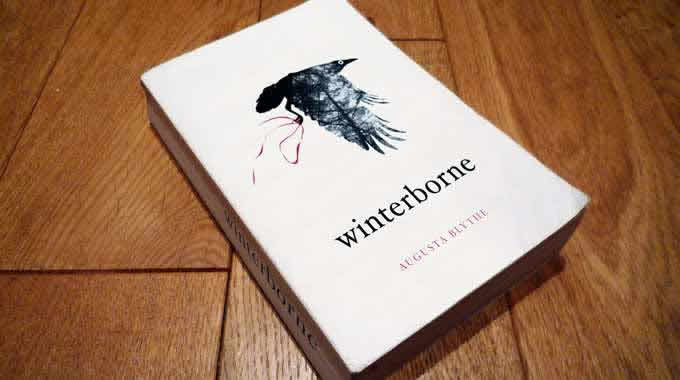 Winterborne book on floor featuring a crow flying on a white background carrying a red ribbon